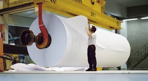 Men checking quality of finished industrial paper roll.