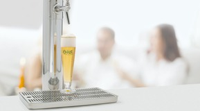 Dispensing equipment with glass of hoesl beer.